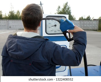Translation from Russian to column - liters. Gasoline prices even shoot yourself. A man in a blue jacket at a gas station is standing with a gun at his temple. Old gas station, arrow to 20 liters