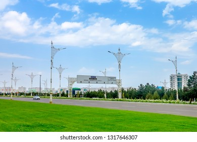 """TRANSLATION:""""Ashgabat Street Names Road Sign."""" Ashgabat Low Intensity Traffic on Roads with White Marble Highrises and Road Signs"""