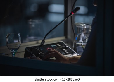 Translator or translation booth at a conference. Hand of a person for simultaneous translating is seen working in a booth. Glass of water next to a translator.