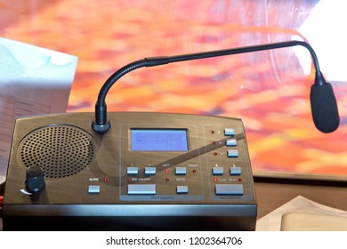 translators cubicle . interpreting - Microphone and switchboard in an simultaneous interpreter booth . Soft focus of wireless Conference microphones and notebook in a meeting room.
