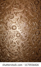 A translucent brown window pane with textured floral pattern and light coming from behind.