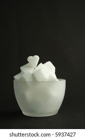 A translucid bowl of white lump sugar, on a black background.