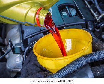 Transmission oil fill up in a car engine with yellow cone spire shape container .