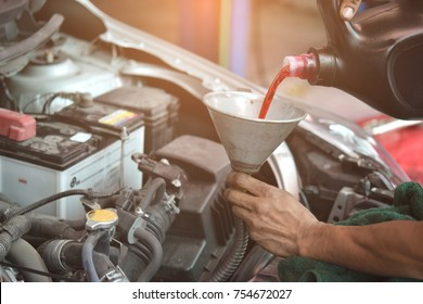 Transmission oil fill up in a car engine with metal cone.