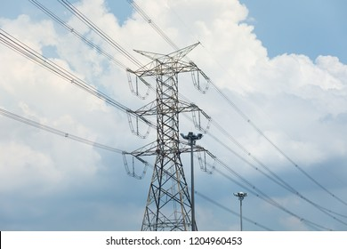 A transmission tower or electricity pylon with blue sky. It is a tall structure, usually a steel lattice tower, used to support an overhead power line.