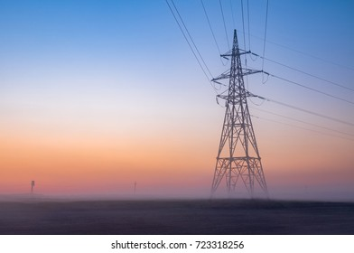 transmission tower in the fog at the background of the dawn sky