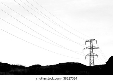 transmission tower with high voltage wires in a dark landscape setting