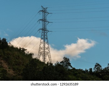 A transmission tower on a green rocky hill with a blue sky background.