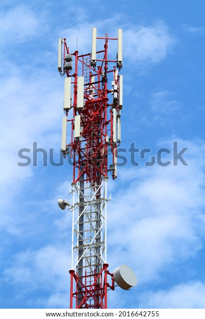 Transmitter tower, red and white color, blue sky. Satellite dishes.