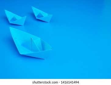 Transnational monopoly business concept origami blue boats paper on blue background