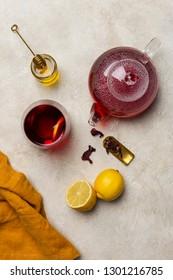 Transparency glass of hibiscus tea (karkade, Agua de flor de Jamaica) with lemon, glass teapot, honey with honey stick and orange napkin at white background.  Concept of healthy lifestyle