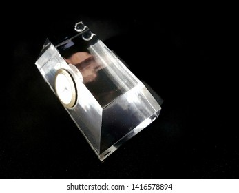 transparent acrylic with a golden watch on black background