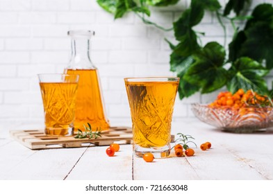 Transparent alcoholic drink from sea-buckthorn on a wooden background. Selective focus.