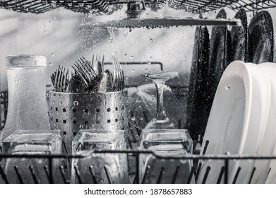 Transparent and black and white dishes as well as cutlery and glasses are washed in the dishwasher, inside view, drops and splashes of water.