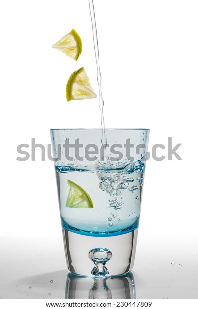 Transparent blue glass of water and lime on a white background