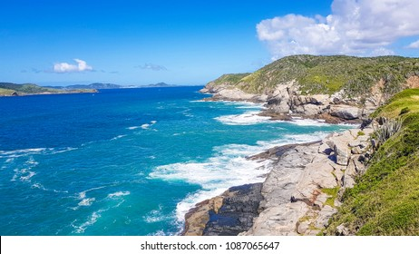 Transparent blue water beach in Arraial do Cabo with rocks and mountains. Rio de Janeiro (Brazil)