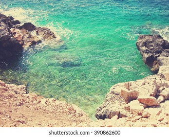 Transparent blue water of the white rocky beach on a sunny summer day. Image filtered in nostalgic, faded, retro, Instagram style with extremely soft focus. Mediterranean sea.