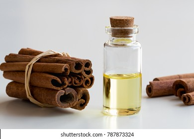 A transparent bottle of cinnamon essential oil with cinnamon sticks on white background