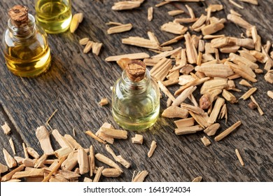 A transparent bottle of essential oil with cedar wood chips