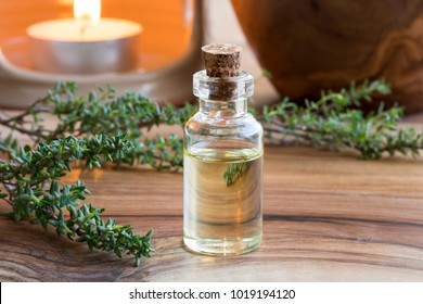 A transparent bottle of thyme essential oil with fresh thyme twigs and an aroma lamp in the background