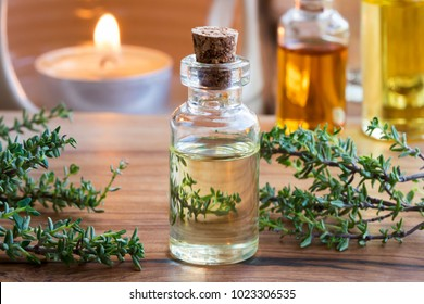 A transparent bottle of thyme essential oil with fresh thyme twigs and a candle in the background