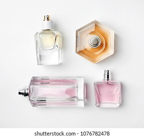 Transparent bottles of perfume on white background