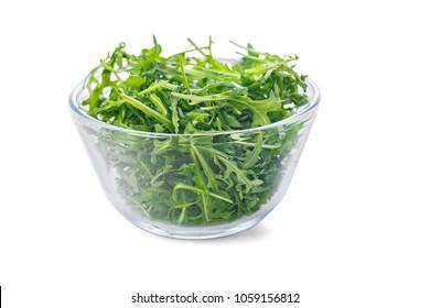 Transparent bowl of fresh arugula, isolated on white
