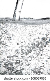 Transparent carbonated drink poured into a transparent container, shot on white background.