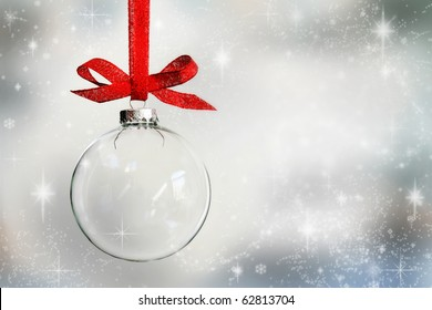 Transparent Christmas ball hanging on red ribbon on snowy winter background