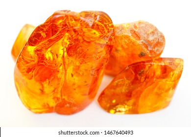 Transparent colored pieces of amber on a white background. Ancient petrified resin. Composition of amber and natural stone. Sun stone. Material for jewelry. Bright color crystal. Amber texture