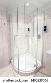 Transparent corner glass shower cabin in white tiled bathroom