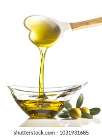 in a transparent crystal bowl flows extra virgin olive oil poured from a spoon with the shape of a heart