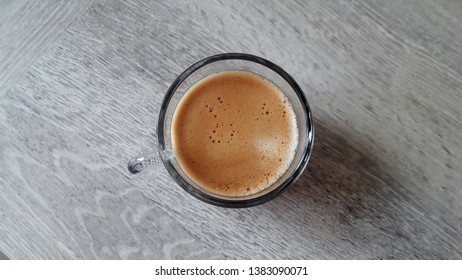 A transparent cup of coffee on grey table background. Frothy hot coffee top view in the middle. Morning energy drink.