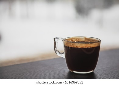 Transparent cup of coffee placed on dark brown laminated wooden surface in front of a window, blurred snow covered street on background.