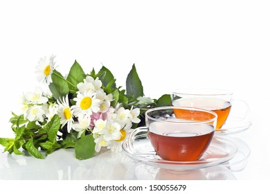 Transparent cup with green tea and fresh herbal bouquet on mirror background