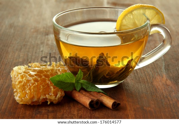 Transparent cup of green tea with honey and cinnamon on wooden background