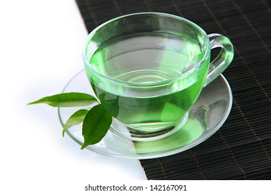 Transparent cup of green tea on bamboo mat, isolated on white