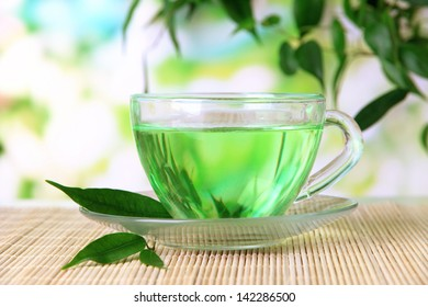 Transparent cup of green tea on bamboo mat, on nature background