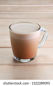 Transparent cup with hot cocoa chocolate on wooden table