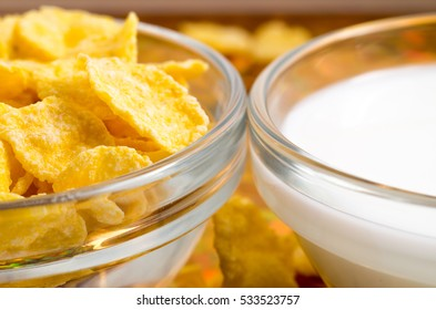 Transparent cup with milk and corn flakes close-up with very little depth of focus