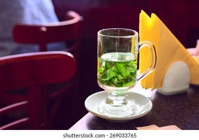 Transparent cup of mint tea on the table in cafe