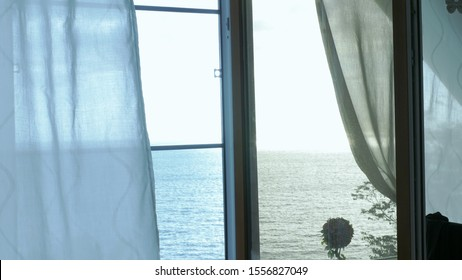 Transparent curtain on the window overlooking the sea, gently moved by the wind. Sunlight.