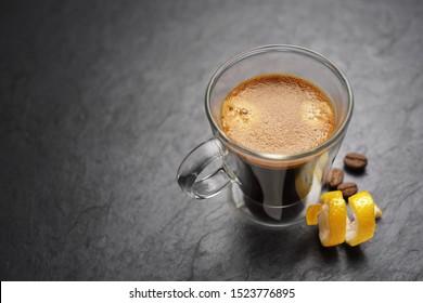 Transparent double wall glass espresso coffee mug with lemon peel on black slate background