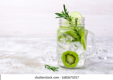 Transparent drink with fruit and rosemary in glass on a light background. Selective focus.