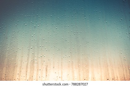Transparent drops of water on the glass surface. Color transition from orange to blue shades. Matte gradient. Ideal background for artistic collages and illustrations.