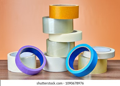 Transparent duct tape for packing and painter's masking tape in small heap on table.