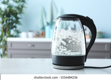 Transparent electric kettle with boiling water on table in kitchen