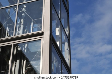 transparent elevator leading to pedestrian bridge in business district of a city