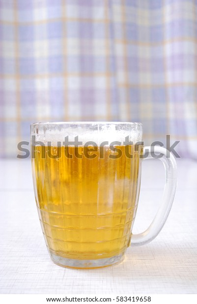 The transparent glass of beer costs on a table