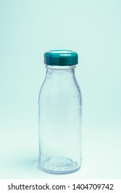 A transparent glass bottle with blue colored tin cap isolated on a white uniform background